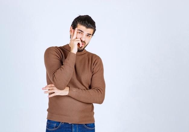 Porträt eines jungen mannes, der gegen weiße wand denkt und steht.