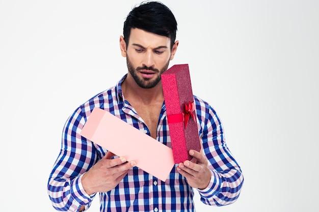 Porträt eines jungen mannes, der geschenkbox öffnet, lokalisiert auf einer weißen wand