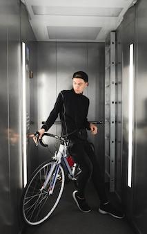 Porträt eines jungen mannes, der im aufzug zusammen mit einem fahrrad reitet.