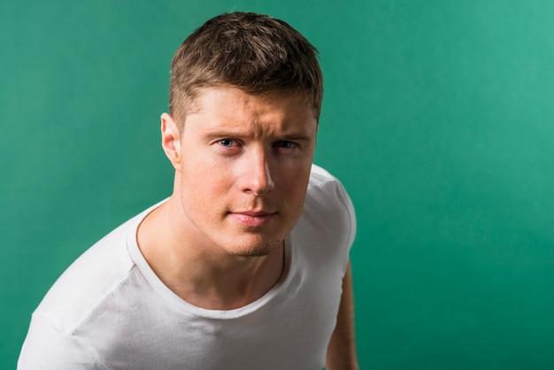 Porträt eines jungen mannes, der misstrauisch kamera gegen grünen hintergrund betrachtet