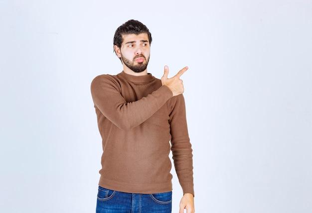 Porträt eines jungen mannes, der mit den fingern auf den kopierraum zeigt