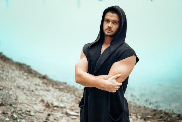 Porträt eines jungen mannes, der mit einem bloßen torso auf einem seehintergrund steht.