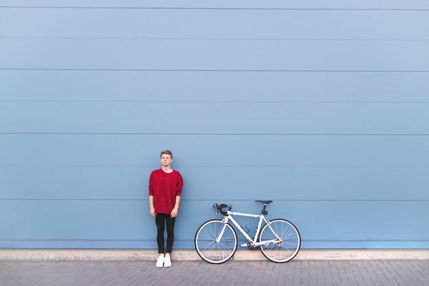 Porträt eines jungen mannes, der mit einem fahrrad auf einem pastellblauen hintergrund steht