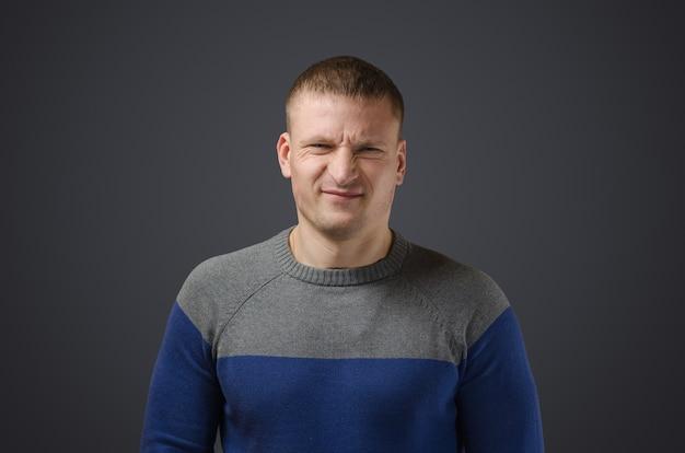 Porträt eines jungen mannes, der mit etwas unzufrieden ist. emotionales foto im studio auf einer schwarzen oberfläche.