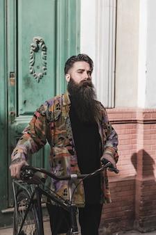 Porträt eines jungen mannes, der mit seinem fahrrad steht