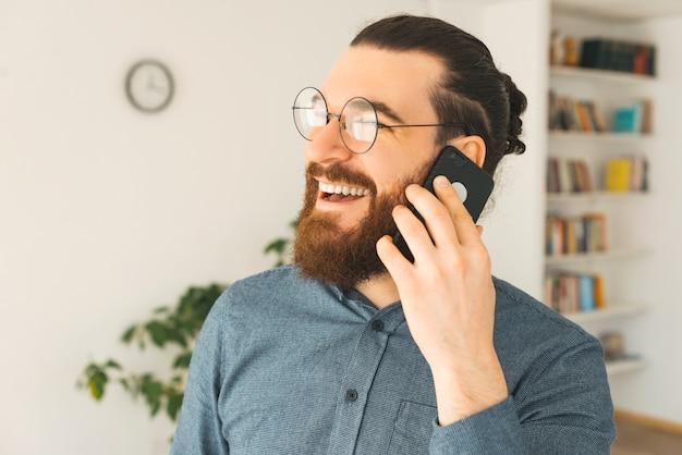 Porträt eines jungen mannes, der mit seinem telefon im büro spricht