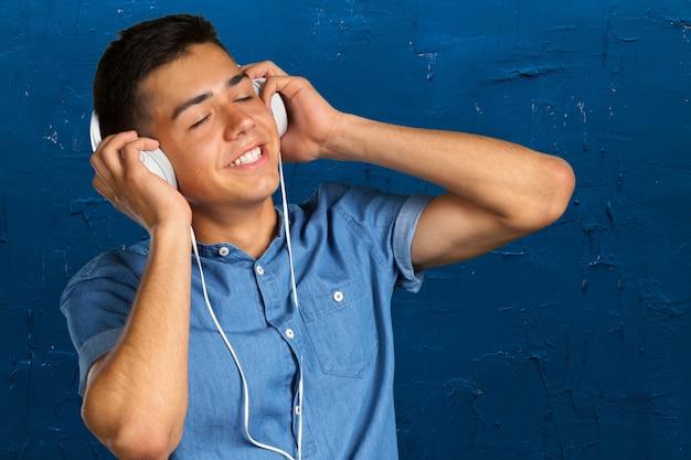 Porträt eines jungen mannes, der musik mit kopfhörern hört