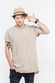 Porträt eines jungen mannes, der pistole gesutre über seinem kopf zeigt, lokalisiert auf einem weißen hintergrund