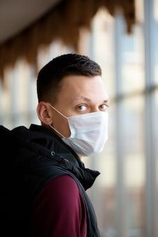 Porträt eines jungen mannes, der schutzgesichtsmaske gegen coronavirus trägt.