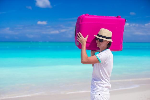 Porträt eines jungen mannes, der sein gepäck auf dem strand trägt