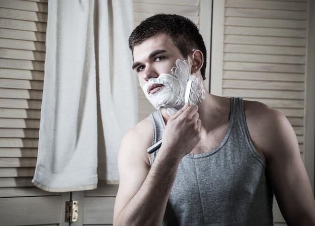 Porträt eines jungen mannes, der sein gesicht im badezimmer während der morgenhygiene rasiert.