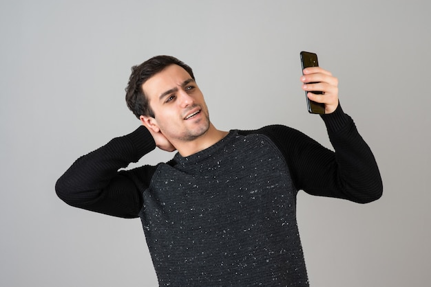 Porträt eines jungen mannes, der sein selfie auf grauer wand macht