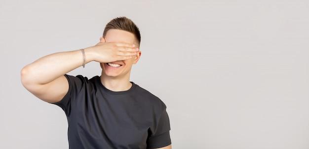 Porträt eines jungen mannes, der seine augen mit seiner handfläche bedeckt und lächelt und auf ein unerwartetes geschenk wartet