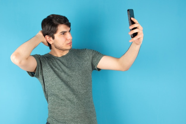 Porträt eines jungen mannes, der selfie mit handy gegen blau nimmt.