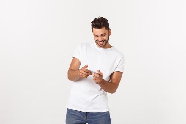 Porträt eines jungen mannes, der videospiele auf handy spielt.