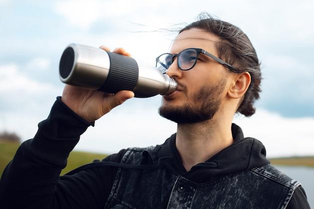 Porträt eines jungen mannes, der wasser aus einer wiederverwendbaren metallflasche trinkt