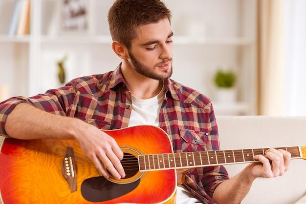 Porträt eines jungen mannes, der zu hause die gitarre spielt.
