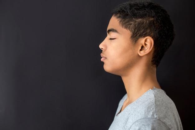 Porträt eines jungen mannes des afroamerikaners mit geschlossenen augen gegen einen schwarzen hintergrund.