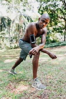 Porträt eines jungen mannes des athleten am park, der das ausdehnen tut, trainiert