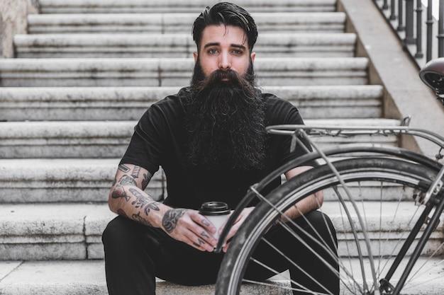Porträt eines jungen mannes des bartes mit seinem fahrrad, das kamera betrachtet