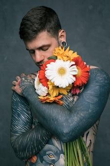 Porträt eines jungen mannes des hippies mit tätowiert auf seinem körper, der die gerberablumen umfasst