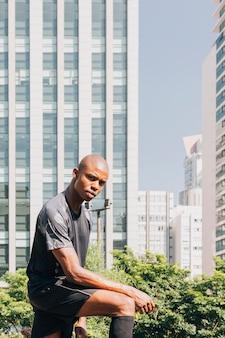 Porträt eines jungen mannes des vertrauensathleten, der die kamera steht gegen gebäude betrachtet