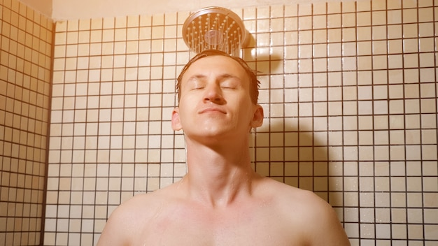 Porträt eines jungen mannes duscht und kämmt sich die haare mit den händen