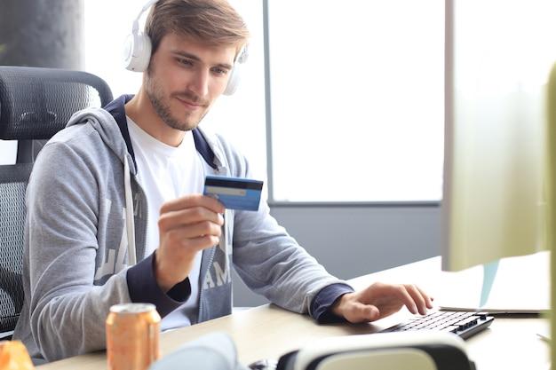 Porträt eines jungen mannes hält und verwendet kreditkarte zum aufladen von spielgeld.