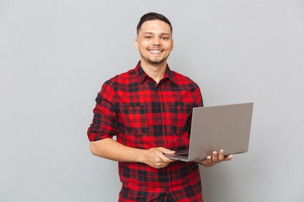 Porträt eines jungen mannes im karierten hemd, das laptop hält