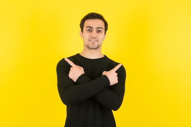 Porträt eines jungen mannes im schwarzen sweatshirt, der an der gelben wand steht und vor der kamera posiert