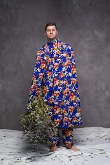 Porträt eines jungen mannes in der blumenkleidung, welche die grünpflanzezweige betrachten kamera hält