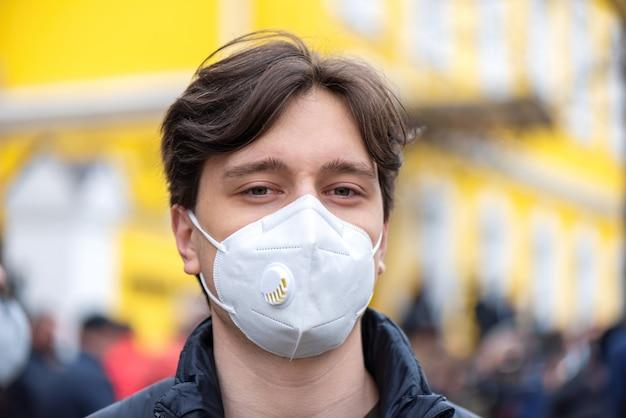 Porträt eines jungen mannes in der medizinischen maske, leute, die für vorgezogene wahlen vor dem gebäude des verfassungsgerichts, chisinau, moldawien protestieren