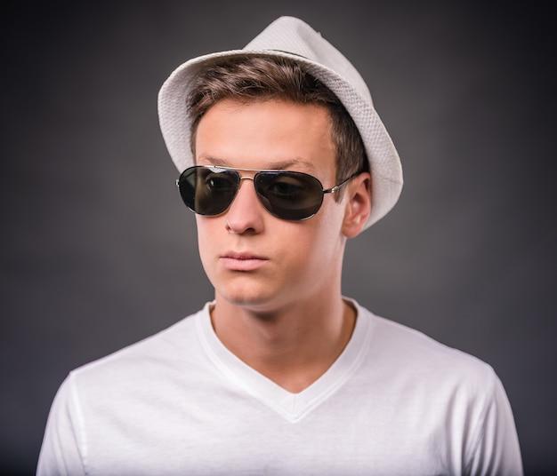 Porträt eines jungen mannes in einem hut und in den gläsern.