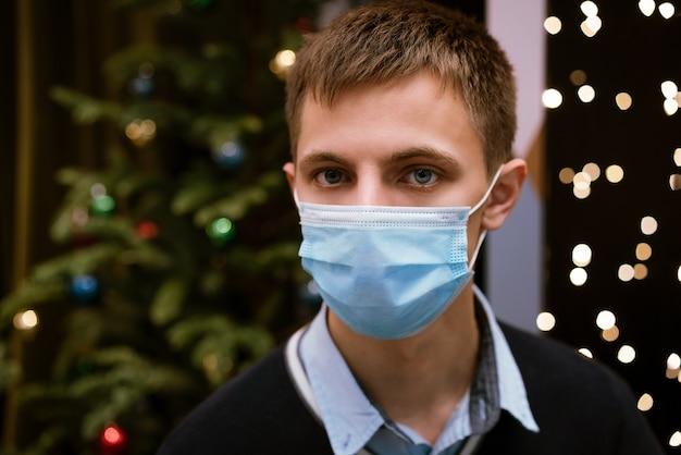 Porträt eines jungen mannes in einer medizinischen maske und einem pullover gegen bokeh und einen weihnachtsbaum