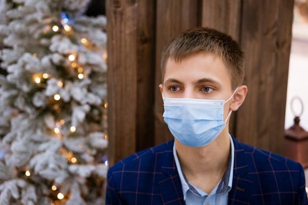 Porträt eines jungen mannes in einer medizinischen schutzmaske in einer blauen jacke an einer holzwand