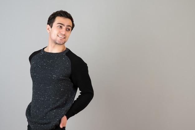 Porträt eines jungen mannes in freizeitkleidung, der die kamera an der grauen wand anschaut