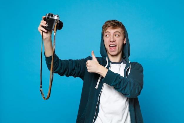 Porträt eines jungen mannes in freizeitkleidung, der selfie auf retro-vintage-fotokamera macht und daumen nach oben isoliert auf blauer wand zeigt. menschen aufrichtige emotionen, lifestyle-konzept.