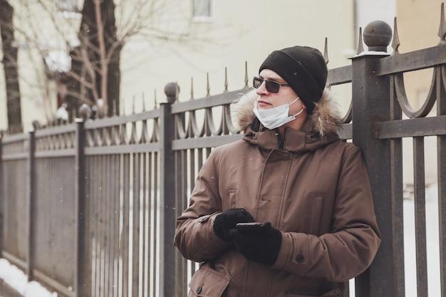 Porträt eines jungen mannes in lässiger winterkleidung mit brille und medizinischer maske auf spaziergang durch die stadt