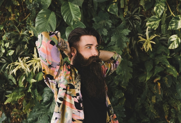 Porträt eines jungen mannes mit dem langen bart, der gegen grünpflanzen steht