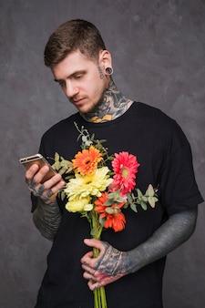 Porträt eines jungen mannes mit durchbohrten ohren und nase, die in der hand blume unter verwendung des smartphone hält