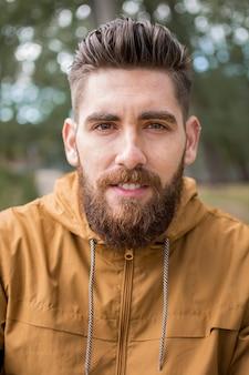 Porträt eines jungen mannes mit einem bart, kaukasisch, mit einem braunen sweatshirt.