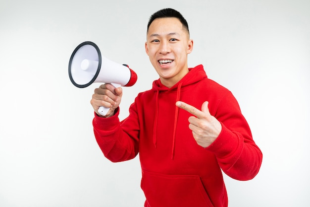 Porträt eines jungen mannes mit einem lautsprecher in den händen auf einem weißen studio
