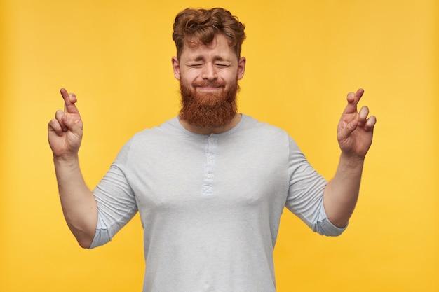 Porträt eines jungen mannes mit großem bart und roten haaren, daumen drücken und augen geschlossen, lippen gepresst, für ein gutes ergebnis auf gelb betend.