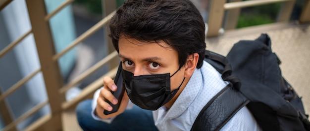 Porträt eines jungen mannes mit maske, den er auf der essenstreppe sitzt und am telefon spricht
