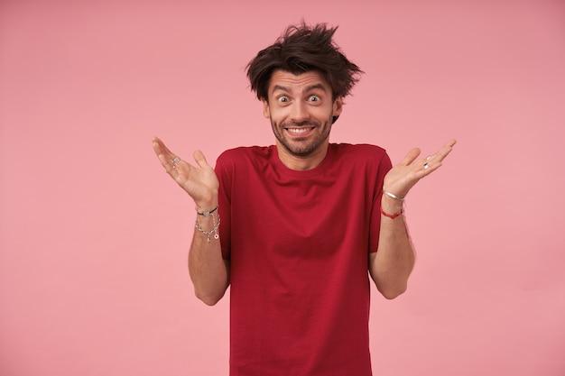 Porträt eines jungen mannes mit offenen augen mit wildem haar, der mit erhobenen handflächen steht, freizeitkleidung trägt, mit breitem lächeln schaut und augenbrauen hochzieht