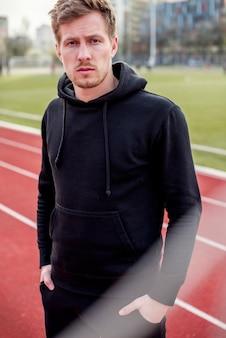 Porträt eines jungen mannes mit seinen händen in der tasche, die auf rennstrecke steht