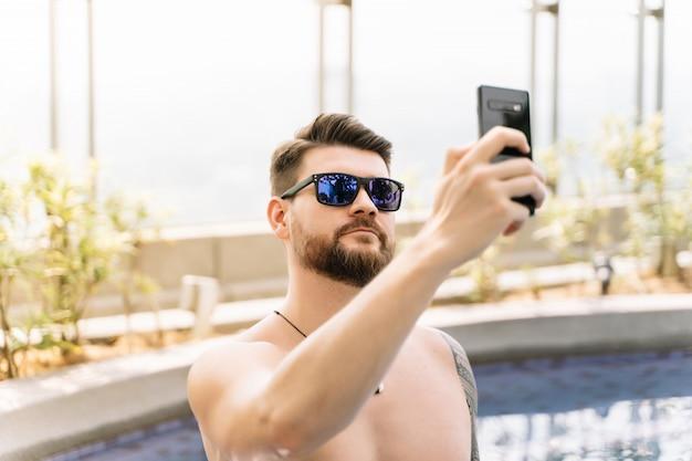 Porträt eines jungen mannes mit sonnenbrille und einer kette, die ein selfie in einem pool macht