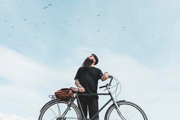 Porträt eines jungen mannes mit tasche auf seinem fahrrad, das die vögel fliegen in den himmel betrachtet