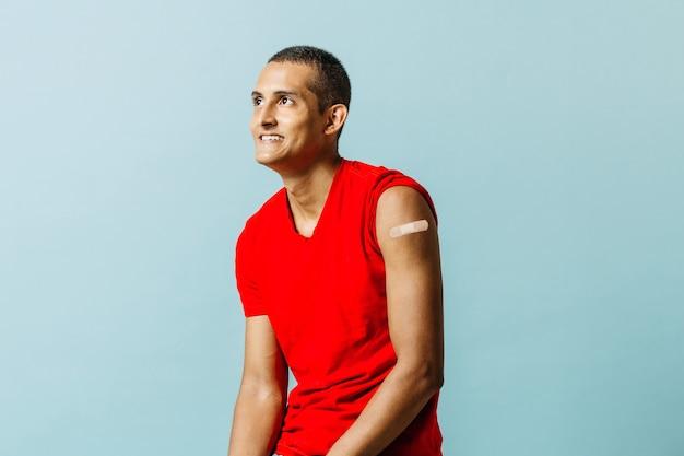 Porträt eines jungen mannes mit verband am arm nach impfung