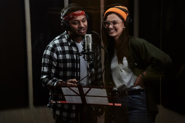 Porträt eines jungen mannes und einer frau im duett, die noten sehen, die in ein kondensatormikrofon singen